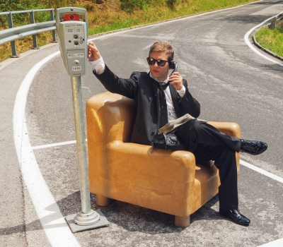 businessman sitting on armchair in middle of the road